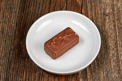 Chocolate bar on a brown wooden table Stock Images