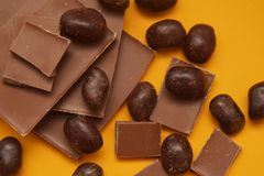 Chocolate Bar and Chocolate Pieces over Yellow Background. Sweet Dessert. top view. Royalty Free Stock Images