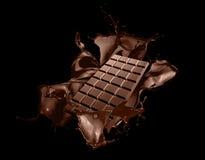 Chocolate bar with chocolate splash on black background stock photography