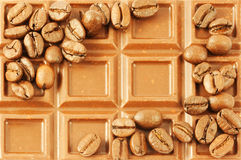 Chocolate bar with coffee beans as background Stock Image