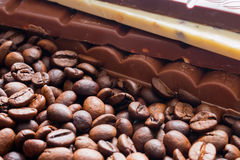 Chocolate bar on coffee beans background Royalty Free Stock Images