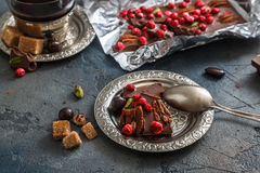 Chocolate bar with dry berries on silver vintage plate, close view, dark background stock photography
