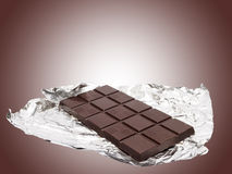 Chocolate bar. With foil against brown background Royalty Free Stock Photo