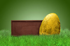 Chocolate bar and golden Easter egg. On grass on green background Royalty Free Stock Photography