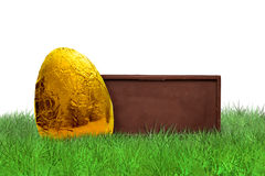 Chocolate bar and golden Easter egg. On grass on white background Stock Images
