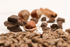Chocolate bar, hazelnut and cinnamon on wooden background, close-up Royalty Free Stock Photo