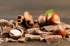 Chocolate bar, hazelnut and cinnamon on wooden background, close-up Stock Photo