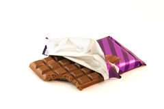 Chocolate bar with a missing bite over white. Chocolate bar isolated on white with a missing bite in the wrapper Stock Photos