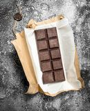Chocolate bar in a paper wrapper. On a rustic background Stock Photography