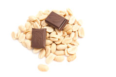 Chocolate bar and peanuts on white. Chocolate bar and heap of peanuts on white royalty free stock photography