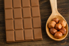 Chocolate bar and peeled hazelnuts in spoon Royalty Free Stock Photo