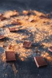 Chocolate bar pieces, cocoa powder and coffee beans on dark stone background. Background with chocolate. Slices of chocolate. Swee. T food photo concept stock photos