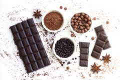 Chocolate bar and pieces with ingredients for cooking sweet food isolated top view