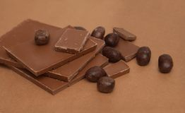 Chocolate Bar and Chocolate Pieces overBrown Background. Sweet Dessert. top view. Stock Photo