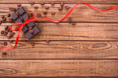 The chocolate bar with red ribbon and cocoa beans Royalty Free Stock Photos