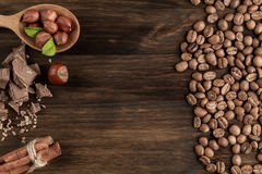 Chocolate bar, shelled hazelnuts, roasted coffee beans, cinnamon on wooden background Stock Image