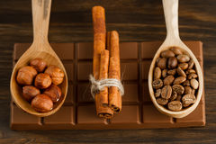 Chocolate bar, shelled hazelnuts, roasted coffee beans, cinnamon on wooden background Royalty Free Stock Image