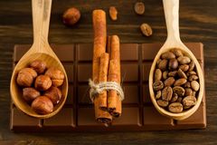 Chocolate bar, shelled hazelnuts, roasted coffee beans, cinnamon on wooden background Stock Photos