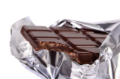 A chocolate bar in a silvery foil. With a bite isolated on white royalty free stock photography