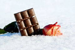 A chocolate bar in the snow with a rose. Delicious chocolate in the snow with a rose Royalty Free Stock Images