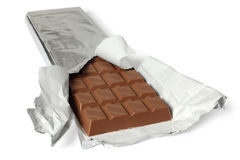 Chocolate bar with torn wrapper. A photo of a large bar of milk chocolate. Shallow depth of field, focusing on the top of the first row. Clipping path included Royalty Free Stock Image