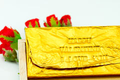 Chocolate bar Wrapped in a gold Ford. Type letters pressing the. Message.  happy valentine i love you   Roses and wooden boxes Stock Photography