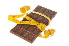 Chocolate bar wrapped with measure tape isolated on white Stock Photos