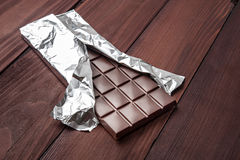 Chocolate bar in wrapper. Chocolate bar in wrapper on the dark wooden background Royalty Free Stock Image