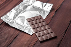 Chocolate bar in wrapper. Chocolate bar in wrapper on the dark wooden background Stock Photo