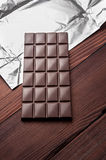 Chocolate bar in wrapper. Chocolate bar in wrapper on the dark wooden background. Top view Stock Images