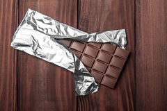 Chocolate bar in wrapper. Chocolate bar in wrapper on the dark wooden background. Top view Stock Photos