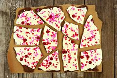 Chocolate bark with candy heart sprinkles over rustic wood. White and dark chocolate bark with candy heart sprinkles on paper against rustic wood Royalty Free Stock Photo