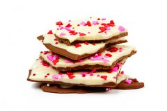 Chocolate bark with candy heart sprinkles stacked over white Stock Image