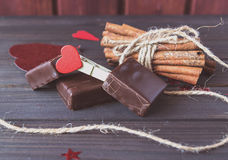 Chocolate bars with cinnamon sticks and cloth pin and cord on wooden planks St.Valentine's Day Stock Photo