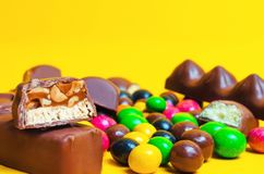 Chocolate bars, colorful candies, sweets on a yellow background. Color stock images