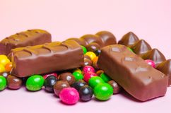 Chocolate bars, colorful candy, sweets on a pink background. Sweet tasty royalty free stock photo