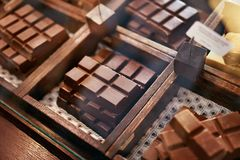 Chocolate Bars In Confectionery Shop Closeup. Handmade Chocolate On Wooden Showcase In Workshop. High Resolution royalty free stock image