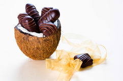 Chocolate bars filled with coconut. Homemade chocolate bars filled with coconut. Served in a half of a coconut on  a white background Stock Photos