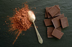 Chocolate bars with heap of cacao powder Stock Photography