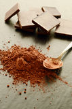 Chocolate bars with heap of cacao powder Stock Images