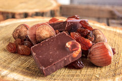 Chocolate bars with nuts and raisins on wooden stump Royalty Free Stock Photos