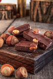 Chocolate bars with nuts on wooden background. Closeup detail of chocolate parts with hazelnuts Royalty Free Stock Images