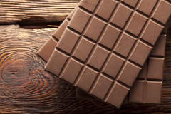 Chocolate bars on old wooden wall Stock Images