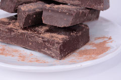 Chocolate bars on a plate. Brown chocolate bars with cocoa powder on a white plate Stock Photos