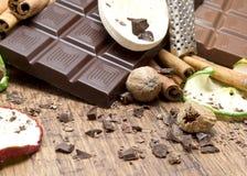 Chocolate bars stack, apples  and cinnamon sticks Stock Photos