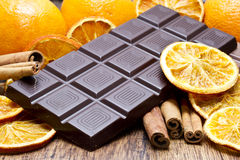 Chocolate bars stack, oranges  and cinnamon sticks Royalty Free Stock Photography