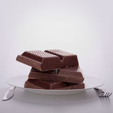 Chocolate bars stack on plate. Stock Photo