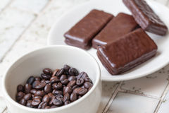 Chocolate bars on white plate with Cup of coffee beans stock photography