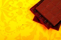 Chocolate bars on yellow background. Different chocolate bars on yellow background stock photography