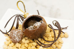 Chocolate bauble with delicious stuffing over crumble and chocol Royalty Free Stock Photos